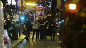 French security moves people in the area of Rue Bichat in the 10th arrondissement of the French capital Paris following a string of attacks on November 13, 2015. At least 18 people were killed as multiple shootings and explosions hit Paris, police said. Police also said there was an ongoing hostage crisis in the Bataclan a concert hall in the French capital. AFP PHOTO / KENZO TRIBOUILLARD (Photo credit should read KENZO TRIBOUILLARD/AFP/Getty Images)